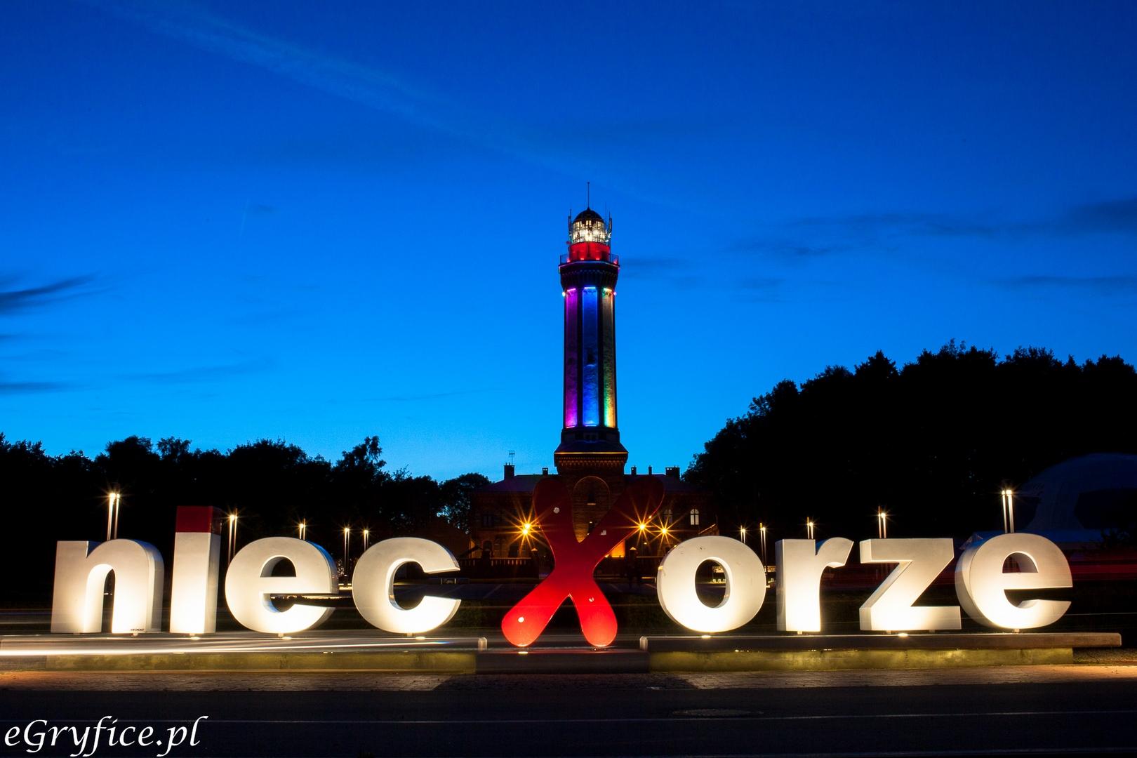 Widok na latarnię morską i wielki napis Niechorze, będący popularnym miejscem do robienia pamiątkowych zdjęć. Turyści mogą liczyć na niskie ceny kwater prywatnych i dostępność lepszych hoteli i pensjonatów.