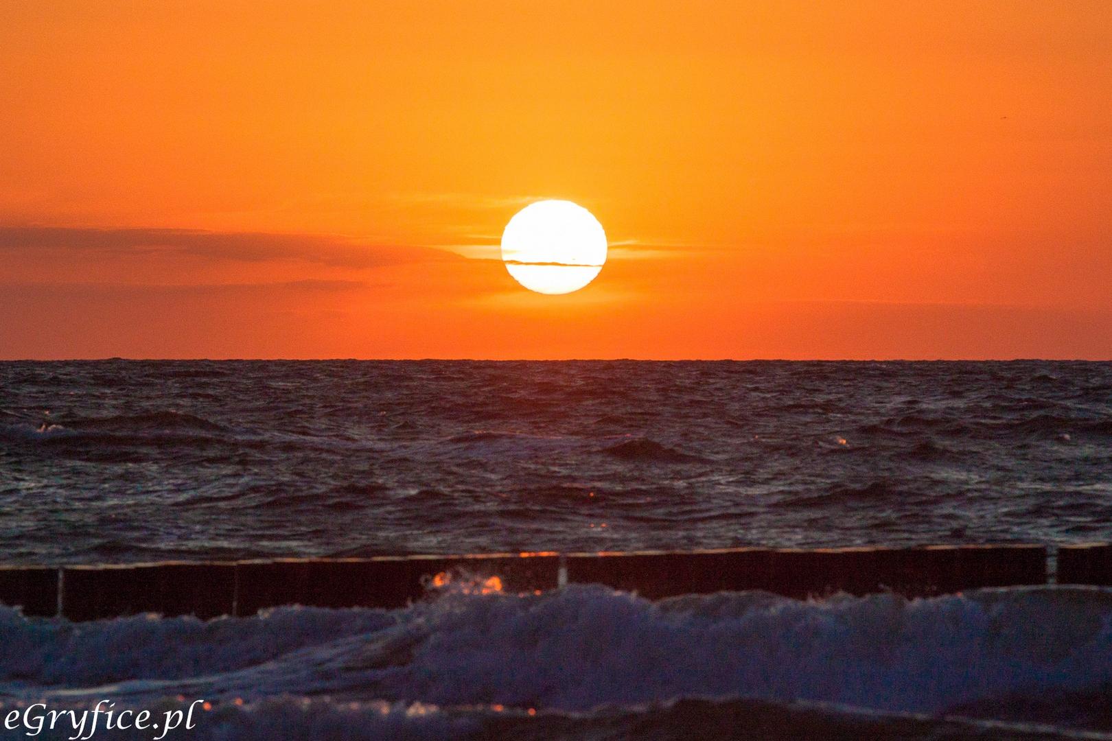 zachód słońca nad morzem w pustkowie, piękne kolory i niemal bezchmurne niebo