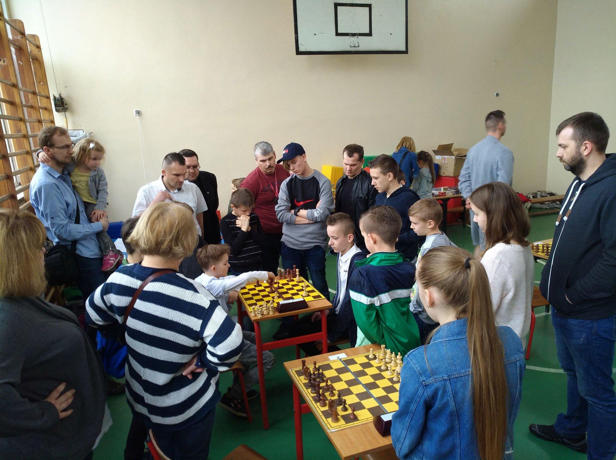 VII Turniej o Nagrodę Mądrej Sowy - zawodnicy i kibice obserwują zacięty pojedynek na pierwszej szachownicy, zmagania szachowe w Gryficach